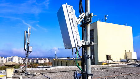 5G mobile telecommunication smart cellular radio network antennas on a mast on the roof broadcasting signal waves over the city on a clear sunny day with blue sky and clouds close up Archivio Fotografico