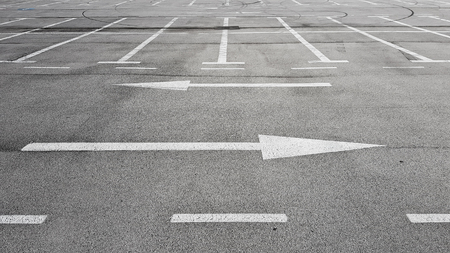 Road sign with two white arrows pointing in different left and right direction on the big empty parking Stock Photo