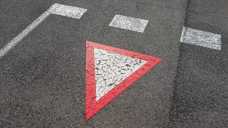 Inverted white with red border triangular road sign yield that you need to wait and give other cars the right to pass
