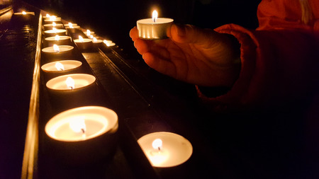 Putting candle on a base in a church