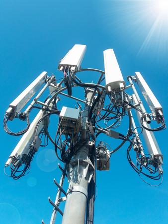 Torre de telecomunicaciones de la estación base de la red de telefonía móvil con antenas celulares inteligentes que irradian y transmiten fuertes ondas de señal digital desde la vista desde la parte superior Foto de archivo