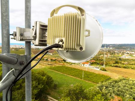 Parabole d'antenne de transmission de liaison micro-ondes sur une construction de tour métallique de réseau cellulaire de télécommunication pointant vers la prochaine station de base transmettant et recevant le trafic de données de téléphone intelligent Banque d'images