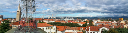 Panoramic view from the roof with cellular network antenna tower on top transmitting mobile signal over old city town Koper, Slovenia covered with black clouds 免版税图像 - 120899182