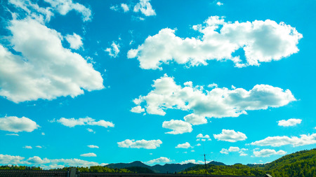 Sunny crystal clear blue summer sky with randomly scattered white clouds