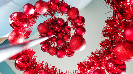 Close up low angle of an modern metal spiral shaped Christmas tree decorated at home with red theme baubles and ornaments
