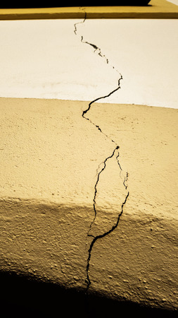 Crack on the building wall surface over the doors extending all the way to the window after an earthquake disaster strike happened