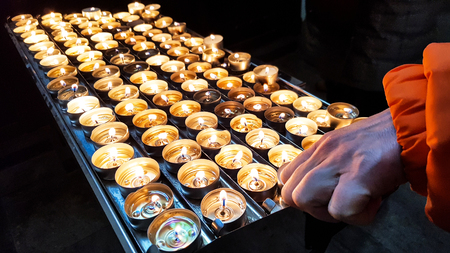 Group of shiny fire burning candles on an metal holder altar in a church Imagens