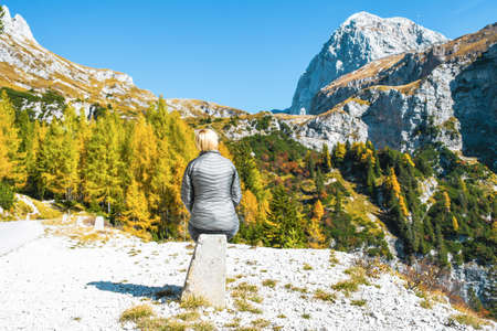 Girl with grey jacket sitting and resting on concrete road pillar on a nice sunny autumn day trip in Julian alps during trekking high in mountains near Mangart saddle, Slovenia 写真素材