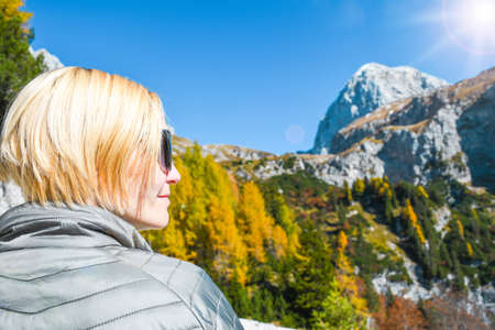 Woman with sunglasses on a nice autumn sunny day on a trip in Julian alps trekking high in mountains near Mangart saddle close up shoot in a back outdoors