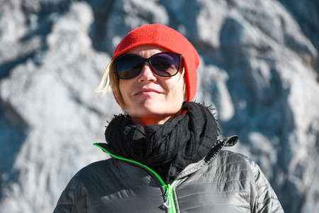 Portrait of a woman with grey jacket and sunglasses on a nice sunny autumn day on a trip in Julian alps trekking high in mountains near Mangart saddle, Slovenia