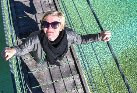 Happy smiling and relaxing woman on an day trip standing on a old wooden hanging bridge over the flowing crystal clear turquoise Soca river, Slovenia 写真素材