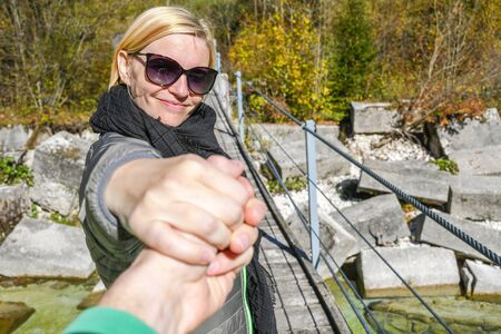 Happy smiling woman standing on a old wooden hanging bridge while holding an arm of her boyfriend with colorful autumn trees and cube shaped rocks in the background 写真素材
