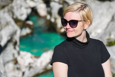 Happy smiling woman with black sunglasses and shirt posing next to a beautiful turquoise colored Soca river canyon in the background, Slovenia 写真素材