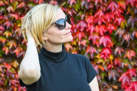 Happy relaxed woman with black sunglasses and shirt holding her arm on the back of her head and posing next to a beautiful autumn colored leaves wall
