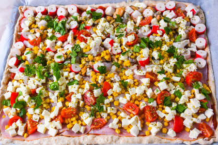 Homemade raw pizza with colorful vegetables and white mozzarella cheese just ready for the oven to bake