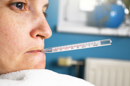 Close up of ill woman with flu and thermometer in her mouth measuring body temperature reaching 40 degrees celsius