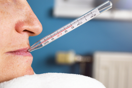 Close up of ill woman with flu and thermometer in her mouth measuring body temperature reaching 39 degrees celsius