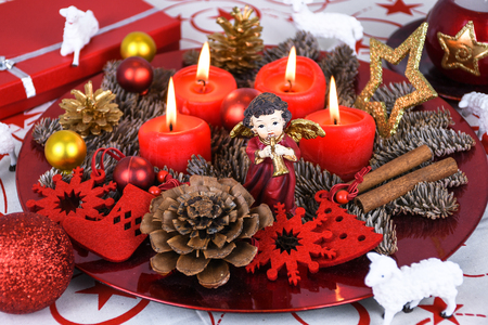 Red Christmas decorated wreath plate with four burning candles on a table cloth surrounded with white sheep and other Xmas theme decoration Imagens