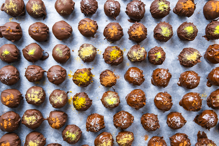 Group of sweet and tasty homemade chocolate balls on a backing paper sprinkled with different spice flavors close up