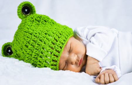 Close up photo of a cute looking adorable newborn baby wearing green frog theme hat with ears peacefully sleeping on a white soft blanket