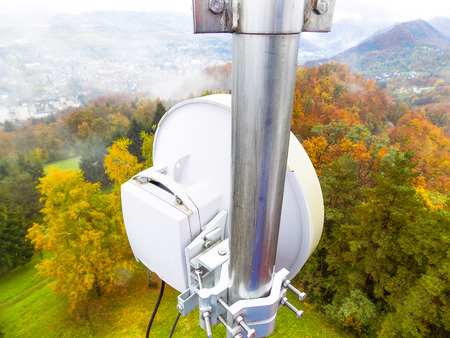 Microwave link transmission antenna dish on a telecommunication cellular network metal tower construction pointing towards next base station transmitting and receiving cell smart phone data traffic