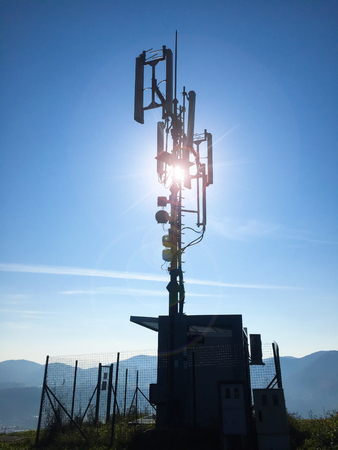 Silhouette of a high cellular telecommunication base station antennas on a sunny day