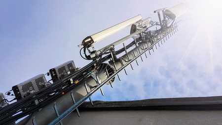 New 5G radio network telecommunication equipment with radio modules and smart antennas mounted on a metal tower radiating strong signal waves over the dense urban city from the roof of the building