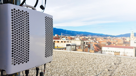 New 5G radio network telecommunication equipment smart radio modules mounted on a metal tower providing power for radio antennas to radiate strong signal waves over the dense urban city Imagens