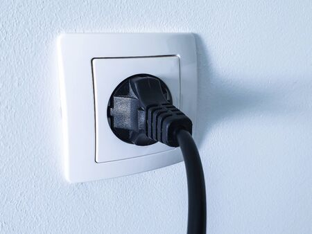 Black electrical power plug connected inside a white plastic power socket on a white wall