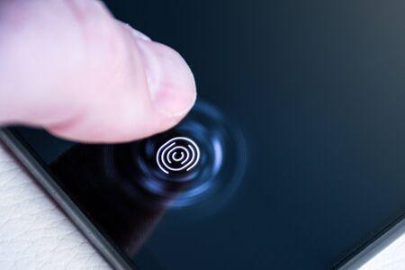 Desbloquear el teléfono con el dedo en un escáner de huellas digitales integrado debajo de la pantalla de cerca Foto de archivo