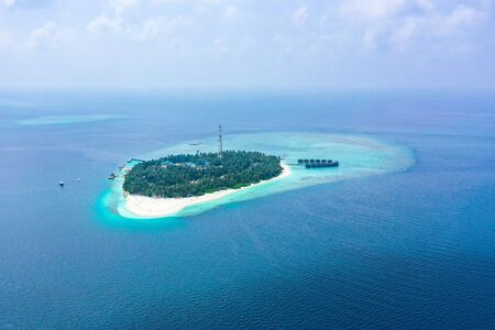 Aerial view of on exotic tropical island paradise with luxurious water villas in turquoise water and surrounded with coral reef