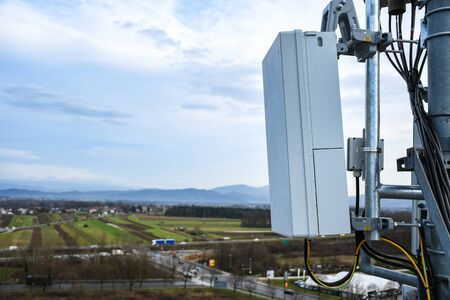 5G new radio telecommunication network antenna mounted on a metal pole providing strong signal waves from the top of the roof across big city Stock Photo
