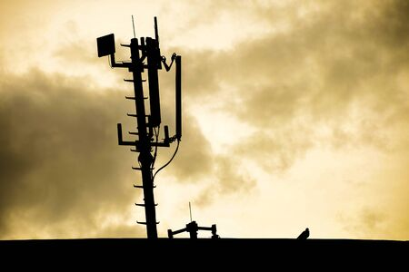 Silhouette of a radio telecommunication network antenna mounted on a metal pole providing strong signal waves from the top of the roof with sunrise and clouds in the background
