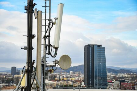 Cellular radio telecommunication network antenna mounted on a metal pole providing strong signal waves from the top of the roof across big city