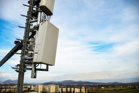 5G new radio telecommunication network antenna mounted on a metal pole providing strong signal waves from the top of the roof across big city