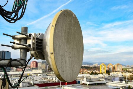 Micro wave radio telecommunication network dish antenna mounted on a metal pole providing transmission strong signal waves from the top of the roof connecting multiple base station across the city
