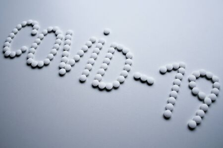 Text phrase Covid-19 sign concept made from white pills on a white background