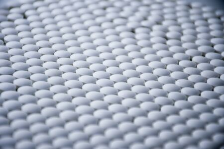 White tablets folded on a pharmaceutical factory production line close up pattern
