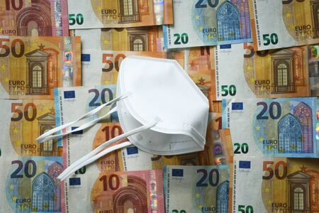 White protective medical face mask laying on the European union money currency Euro different paper notes