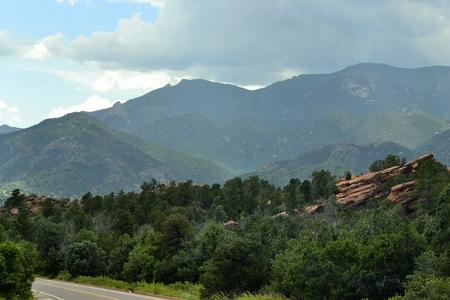 precipitacion: vista muy pintoresca de las montañas y la roca roja con las nubes oscuras que ruedan sobre las cimas de las montañas que cubren el cielo azul oscuro.