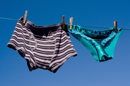 Mens boxer shorts and saucy silk panties together on a suburban washing line in a gender concept. Stock Photo - 10016912