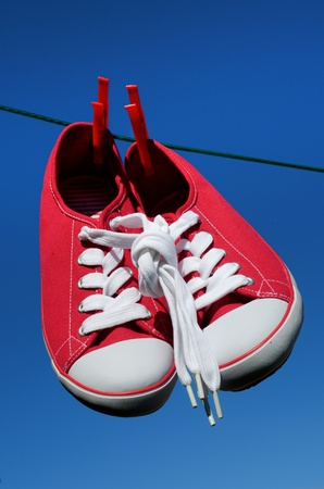 knotted: New sneakers with laces knotted together on washing line against blue sky Stock Photo