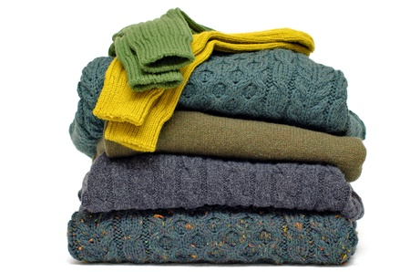 snug: Stack of chunky Irish wool cable knit, Cashmere and Aran winter mens sweaters in fall and winter colours against white