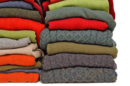 cashmere: Stack of chunky Irish wool cable knit, Cashmere and Aran winter mens sweaters in fall and winter colours against white