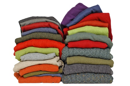 Stack of chunky Irish wool cable knit, Cashmere and Aran winter men's sweaters in fall and winter colours against white Stock Photo - 10084514