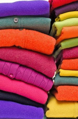 maglioni: Pila di maglioni e cardigan delle donne in vivaci colori vivaci contro il bianco. Archivio Fotografico