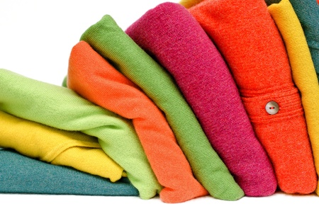 womens: Stack of womens sweaters and cardigans in bright vivid colours against white.