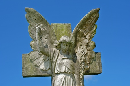 synonymous: Pre 1900 stone statue of angel with wings bright blue sky with clouds from a grave in the famous landmark Milltown Cemetery Belfast, which is the largest Catholic burial ground in Belfast and synonymous with Irish Republicanism.