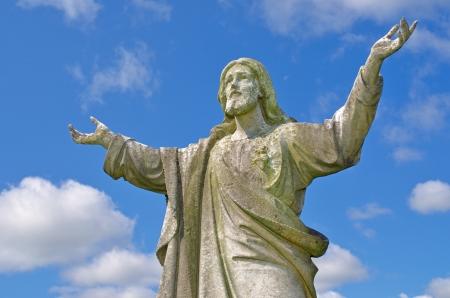 weather beaten: Pre 1900 statua di pietra del tempo di Ges� battuto con le armi giungeva fino al cielo contro il luminoso cielo blu con nuvole provenienti da una tomba nel famoso punto di riferimento Milltown Cemetery di Belfast, che � il pi� grande cimitero cattolico a Belfast e sinonimo di Ir