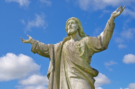 Pre 1900 stone statue of Jesus weather beaten with arms reaching up to heaven against  bright blue sky with clouds from a grave in the famous landmark Milltown Cemetery Belfast, which is the largest Catholic burial ground in Belfast and synonymous with Ir photo